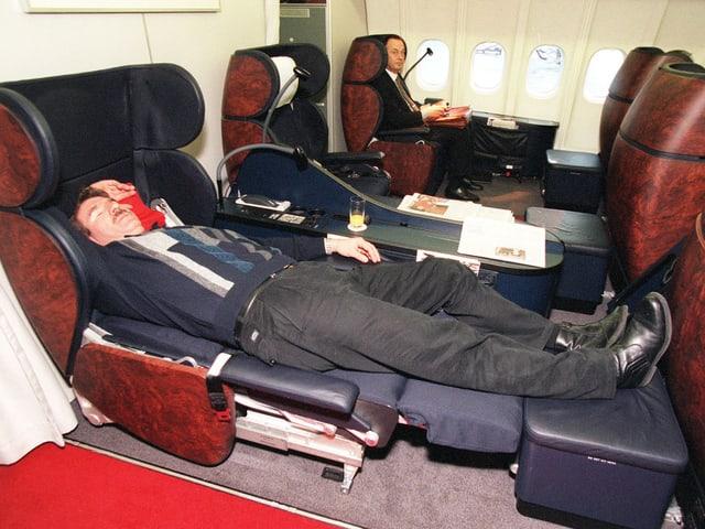 Ein Mann hat einen Sitz zum Bett verwandelt und legt sich hin.