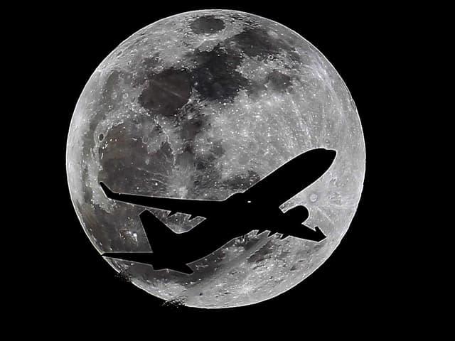Flugzeug vor Mond