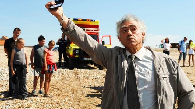 Der Kommissar hält seinen Ausweis in die Luft. Hinten sind die Kinder des Dorfes.