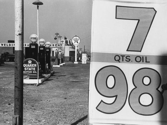 Auf einer schwarz-weissen Fotografie ist eine verlassene Tankstelle zu sehen: Zapfsäulen, rechts ein Schild mit den Ziffern sieben und 98.
