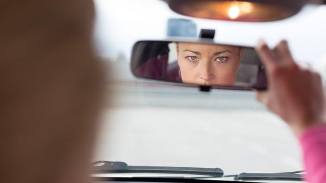 Auto innen: Frau blickt in Rückspiegel und stellt ihn mit der Hand richtig ein.