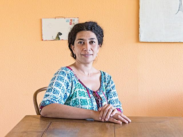 Frida Leon Beraud an einem Holztisch.