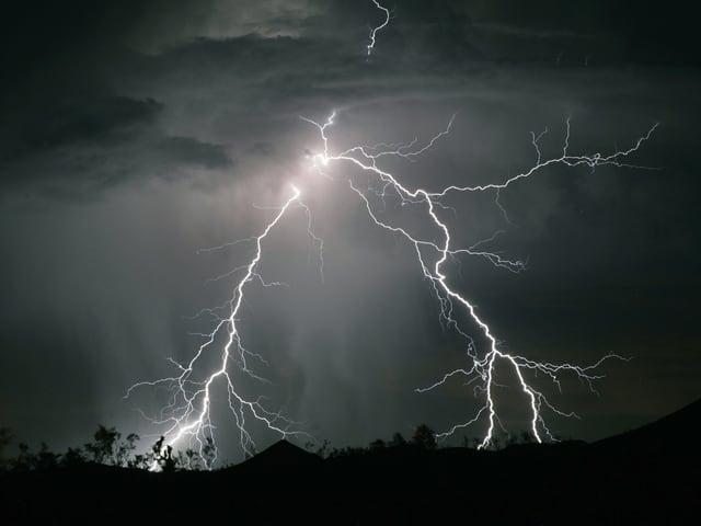 Ein Blitz verästelt sich in zwei Hauptäste und erleuchtet den Nachthimmel.