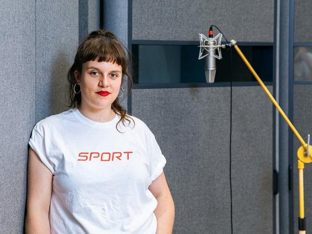Frau in weisem T-Shirt vor einer grauen Wand.