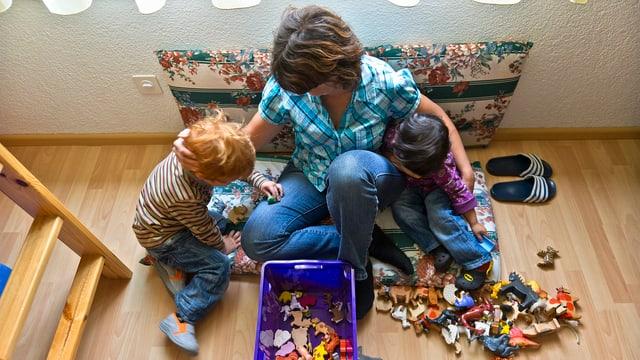 Eine Frau spielt mit zwei Kindern am Boden.