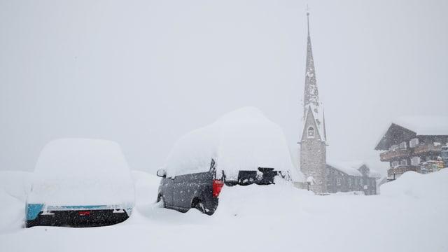 Von Schnee zugedeckte Autos, im Hintergrund eine Kirche im Schneefall.