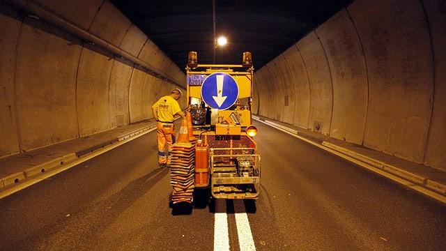 Ein Arbeiter malt eine doppelte Sicherheitslinie auf die Strasse.