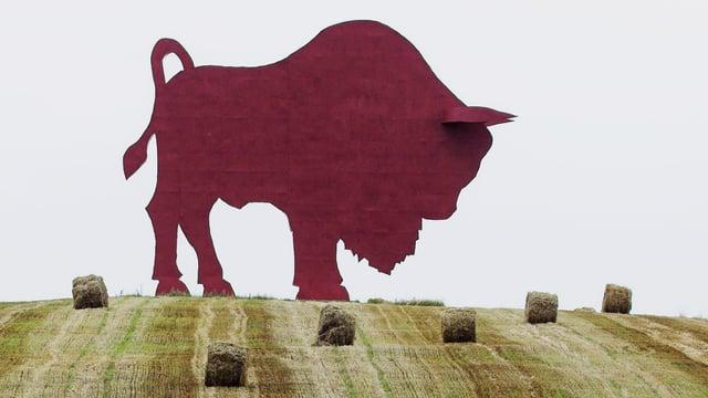 Silhouette einer Wisent-Skulptur auf einem Feld.