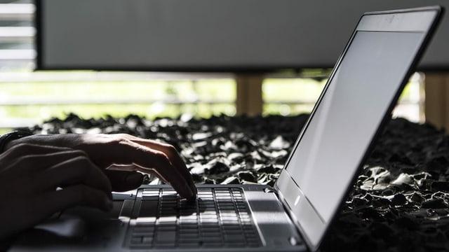 Person sitzt vor Computer.