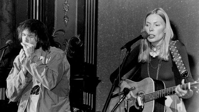 Ein Mann spielt Mundharmonika, eine Frau singt mit Gitarre.