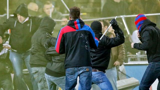 Basler Hooligans stürmen mit Stöcken bewaffnet richtung Aarauer Fan-Sektor.
