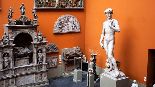 Michelangelos David und andere Stein-Figuren vor der orangefarbenen Wand des V&A Museum