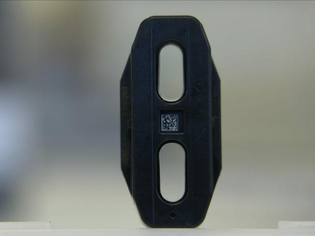 Schwarzes Kunststoffbauteil in der Grösse eines Fünflibers mit zwei ovalen, transparenten Schichten zur Blutanalyse.