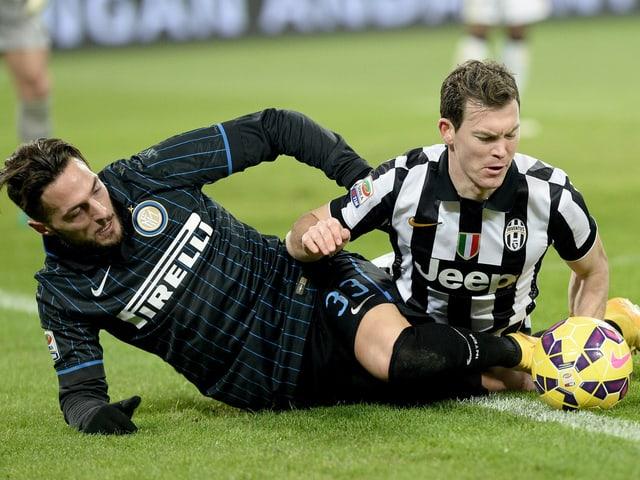 Lichtsteiner liegt mit einem Gegenspieler am Boden und schaut den Ball an.
