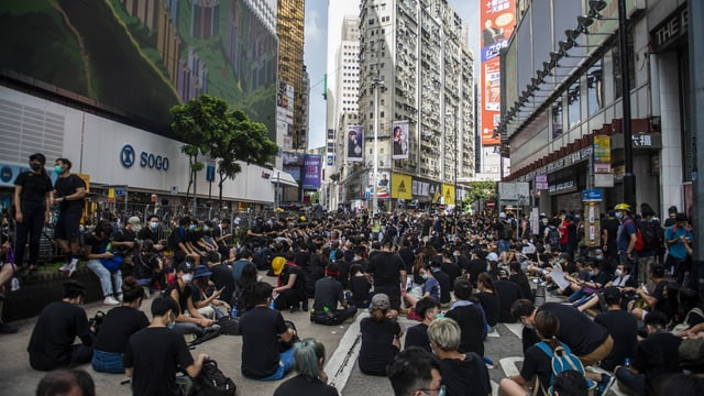 Menschen sitzen auf einer Strasse in Hongkong.