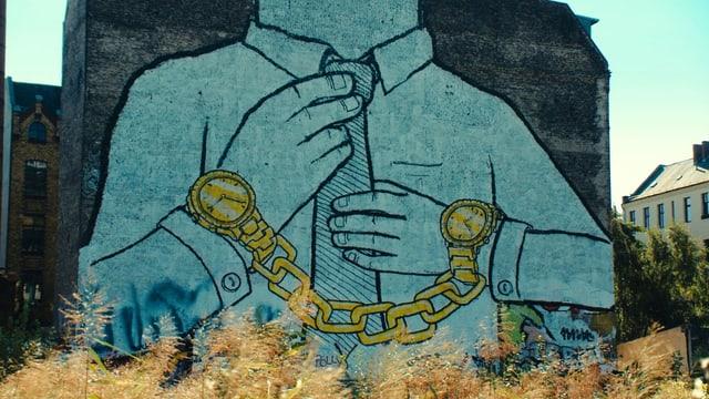 Ein an eine Hauswand gemaltes Bild zeigt einen Mann mit Krawatte, der an beiden Armen eine Uhr trägt; dabei sind die beiden Uhren mit einer schweren Kette verbunden.