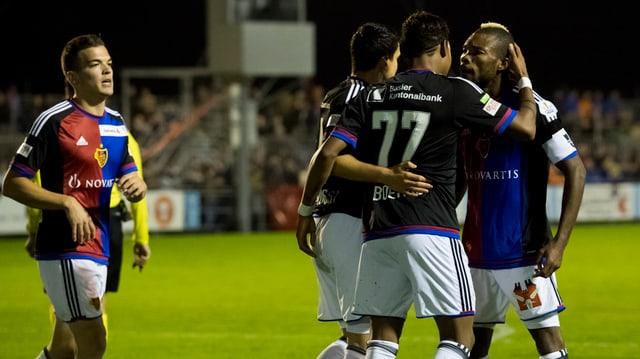 Drei Spieler des FC Basel umarmen sich, ein vierter stösst dazu.