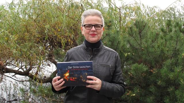 Judith Rickenbach mit ihrem Buch vor zwei Büschen
