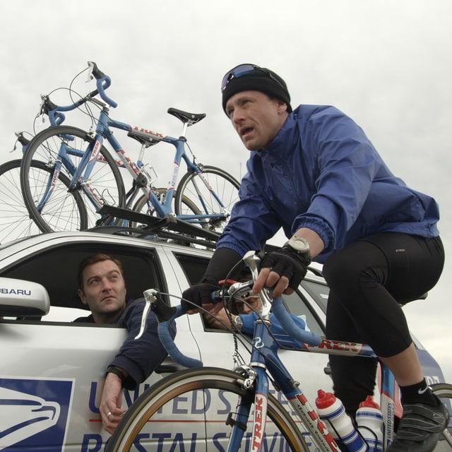 Lance Armstrong fährt auf seinem Fahrrad neben seinem Coach, der im Auto sitzt.