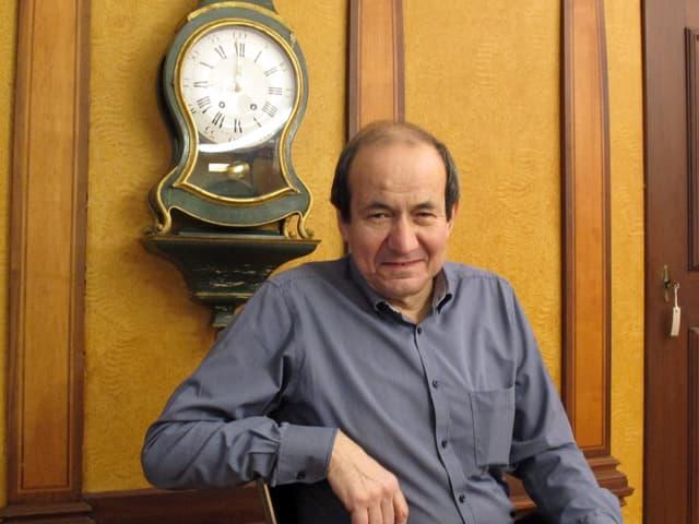Stadtrat Urs Hunziker in seinem Büro vor einer Wanduhr.