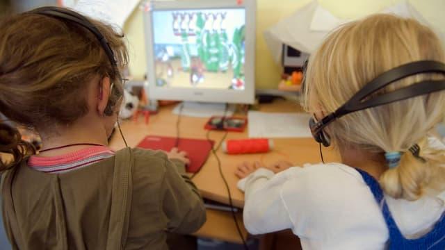 Zwei Unterstufen-Schülerinnen mit Kopfhörer vor Bildschirm.