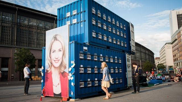 Zwei blaue Schiffscontainer auf einem öffentlichen Platz. Auf der Seite gross ein Porträt-Foto.