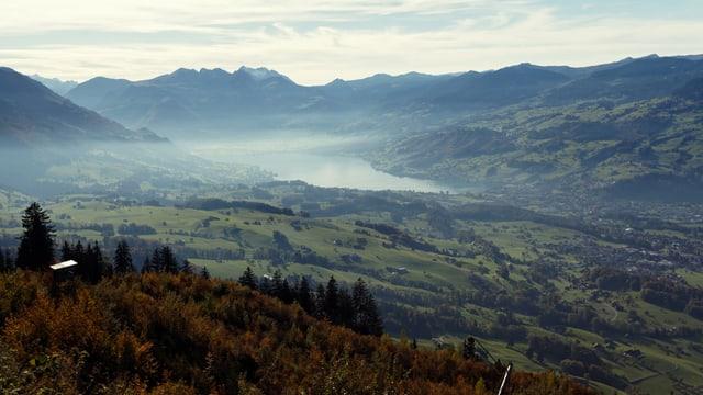 Aussicht auf ein Tal mit einem See, über dem Dunst aufsteigt.