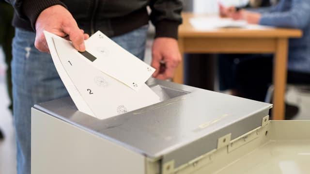 Abstimmungsurne mit Wahlzettel.