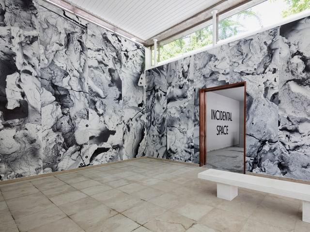 Bicl in einen Raum, in dem eine weisse Bank steht und dessen Wan aussieht wie eine Steingrube.