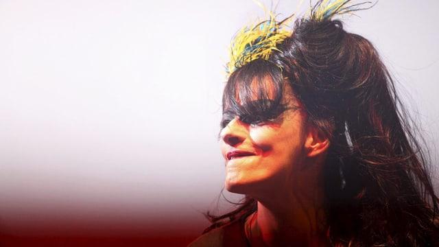 Nina Hagen auf der Bühne. Sie trägt eine bunte Feder im Haar.