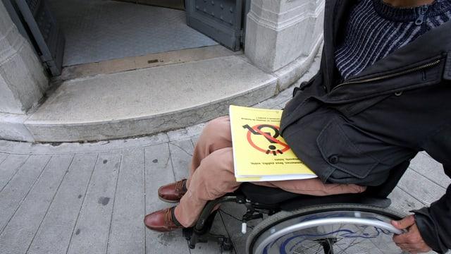 Ein Rollstuhlfahrer vor einem Hauseingang mit einer Türschwelle