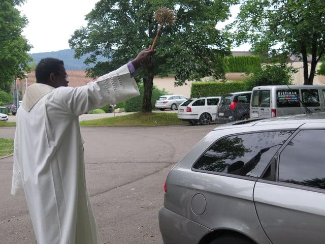 Pfarrer segnet Auto.