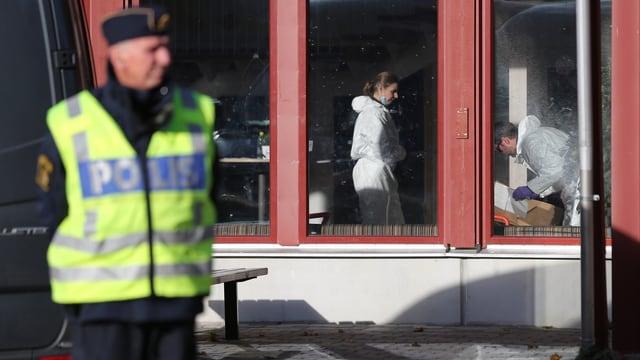 Ein schwedischer Polizist steht vor der Schule, darin untersuchen Spezialisten in weissen Overalls den Tatort.