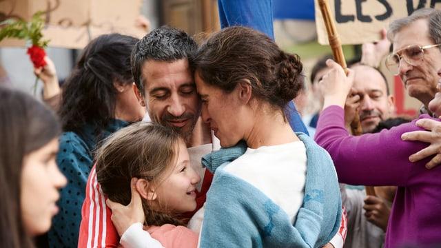 Inmitten einer grösseren Gruppe umarmt sich eine Familie mit Vater, Mutter, Kind. Es scheint eine Wiederzusammenkunft zu sein.