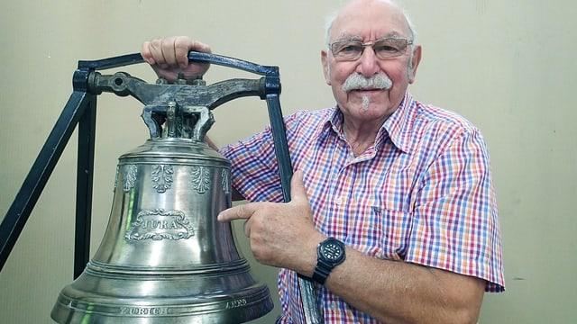 Ein alter Mann mit Schnauz steht stolz neben einer politierten Schiffsglocke, in welche der Name «Jura» eingraviert ist.