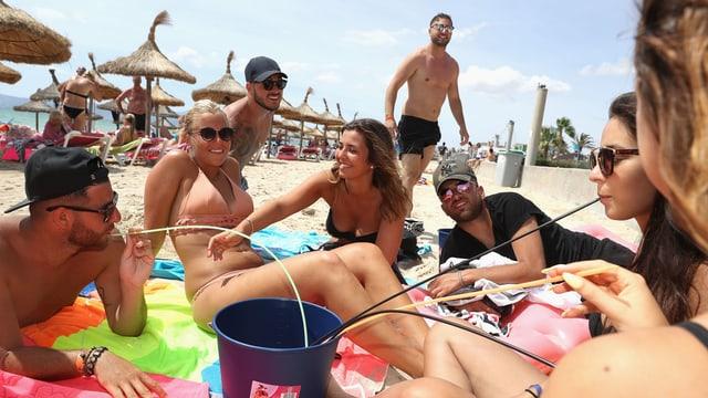 Mehrer junge Menschen sitzen am Strand, in der Mitte ein Eimer mit langen Trinhalmen.