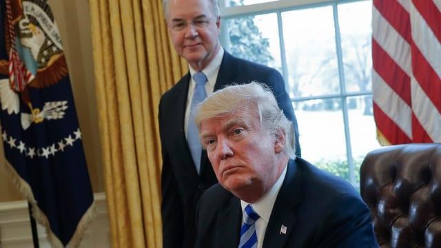 Donald Trump sesa cun ina fatscha indignada en l'Oval Office ed ignorescha a Price che stat suenter el.