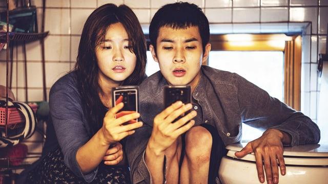 Filmszene: Zwei junger Mann und eine junge Frau sitzen neben einer Toilettenschüssel und schauen aufs Smartphone.