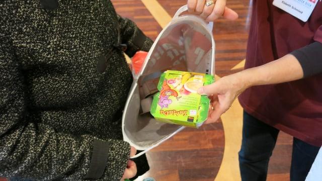 Eine Verantwortlich gibt einer Frau Yoghurt in die Plastiktüte.