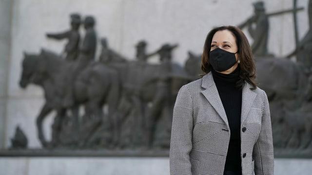 Harris mit Maske vor einem Denkmal.