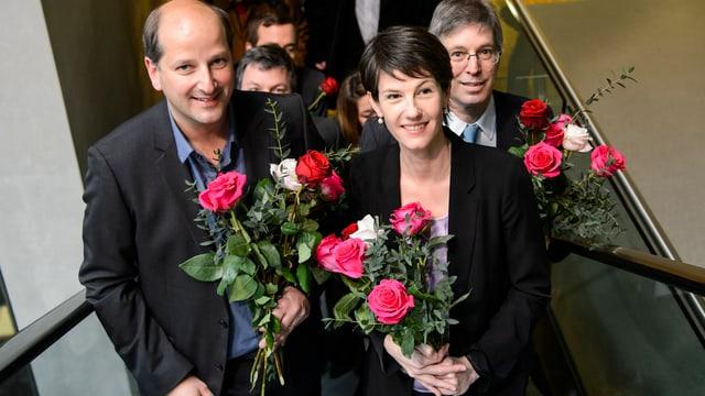 Die strahlenden Gewinner mit Rosen auf einer Treppe.
