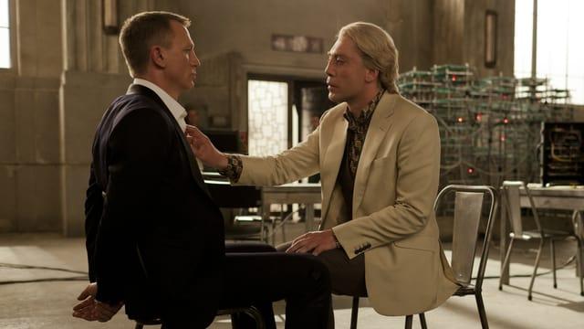 Ein Mann sitzt gefesselt auf einem Stuhl, vor ihm sitzt ein anderer Mann.