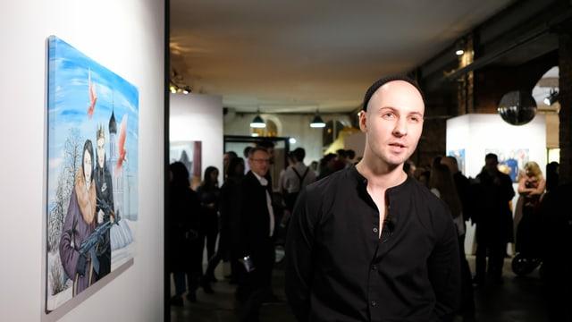 Pasmur Ratschujko an der Vernissage vor einem seiner Bilder.
