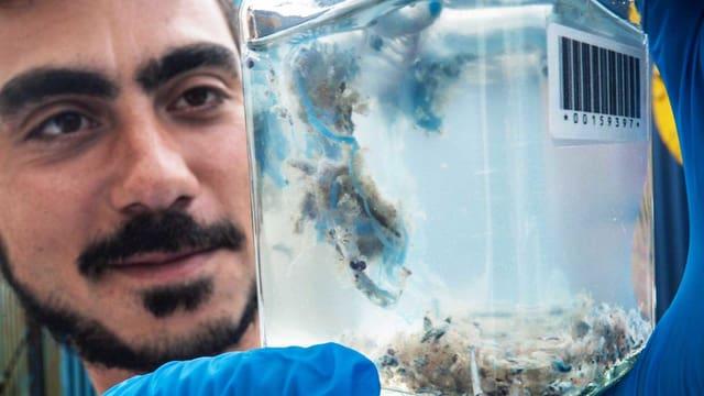 Mann betrachtet ein Glas, in dem eine Portugiesische Galeere schwimmt.