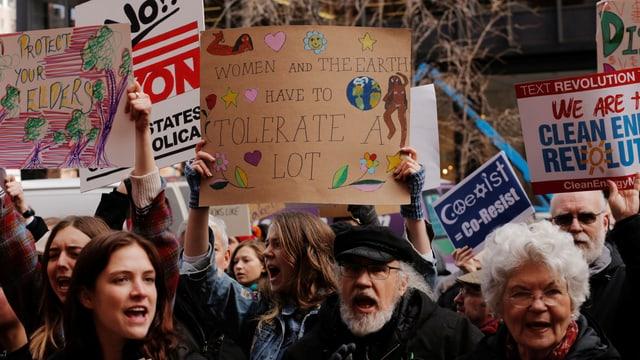 Menschen halten Plakate hoch und rufen Parolen.