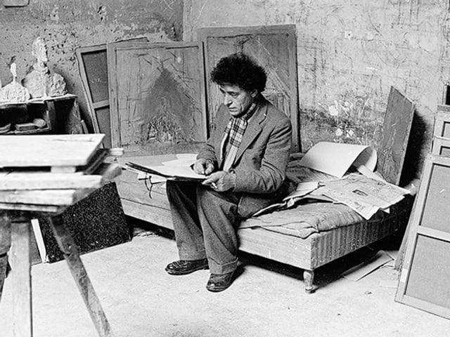 Alberto Giacometti sitzt zeichnend auf dem Bett.