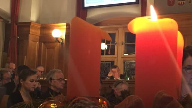 Im Vordergrund drei Kerzen, im Hintergrund ein Mann, der seinen Kopf auf die Hand stützt.
