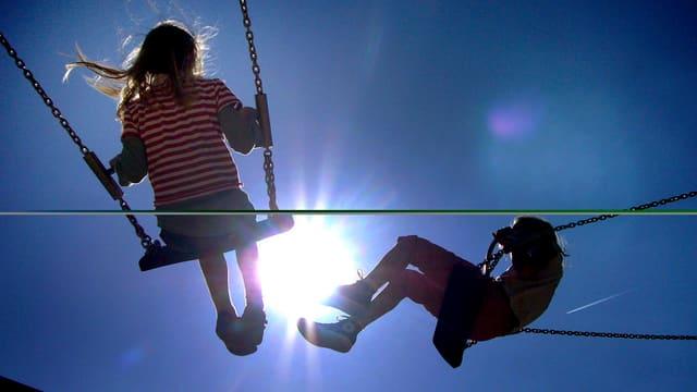 Zwei Kinder auf zwei Kinderschaukeln vor der Sonne.