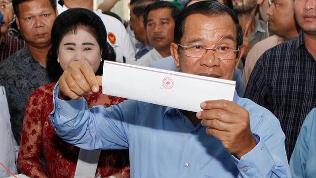 Hun Sen hält seinen Wahlzettel in die Kameras.