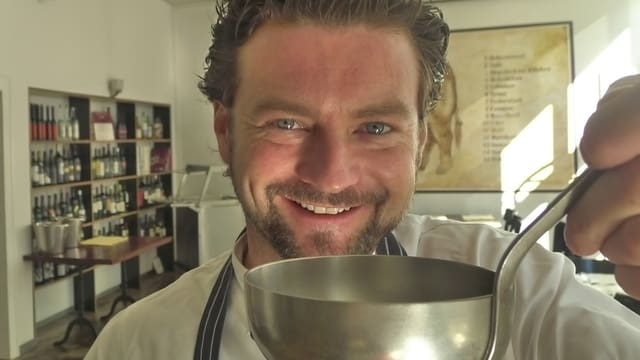 Zu sehen ist der Koch Jann Hoffmann mit einem grossen Suppenschöpflöffel vor dem Mund.